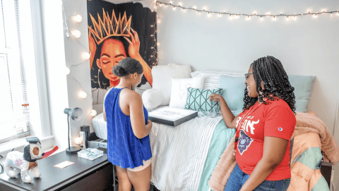 Young women setting up their residence hall room.